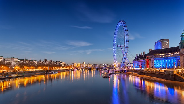 A long bridge over a body of water with London Eye in the background