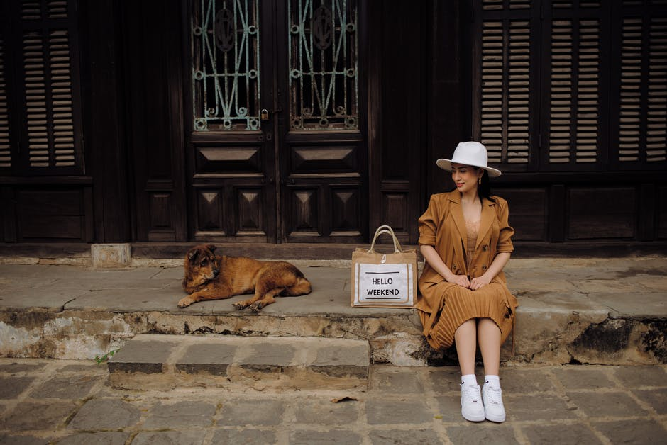 A woman sitting on a bench in front of a building